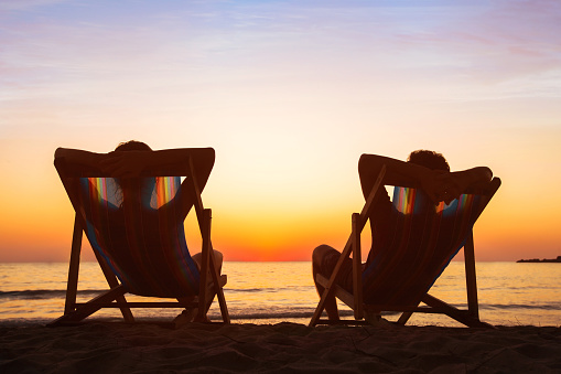 istock happy couple relaxing in beach hotel  at sunset, honeymoon 623189762