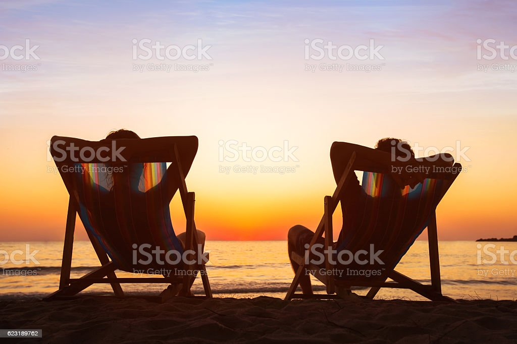 happy couple relaxing in beach hotel  at sunset, honeymoon stock photo