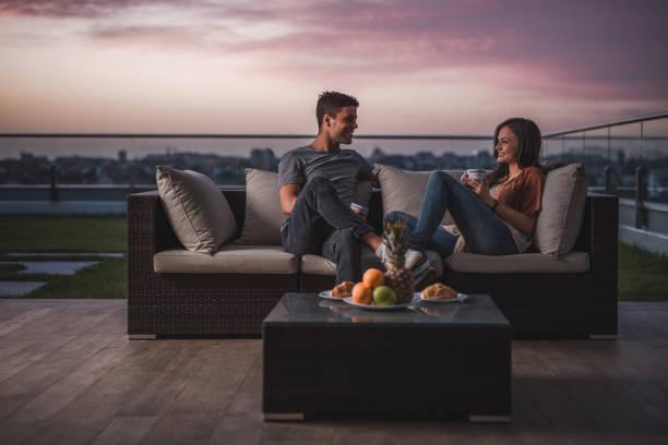 Casal feliz, relaxando em um pátio no crepúsculo e se comunicando. - foto de acervo