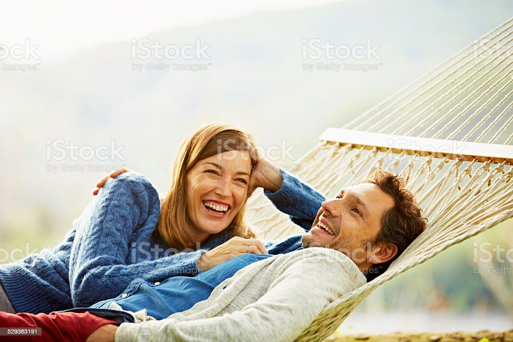 Happy couple relaxing on hammock stock photo