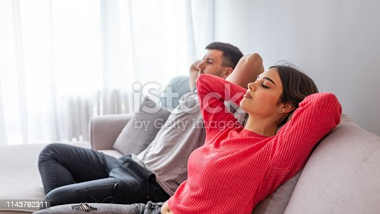 938682762istockphoto Happy couple relaxing on the couch at home in the living room 1143762311