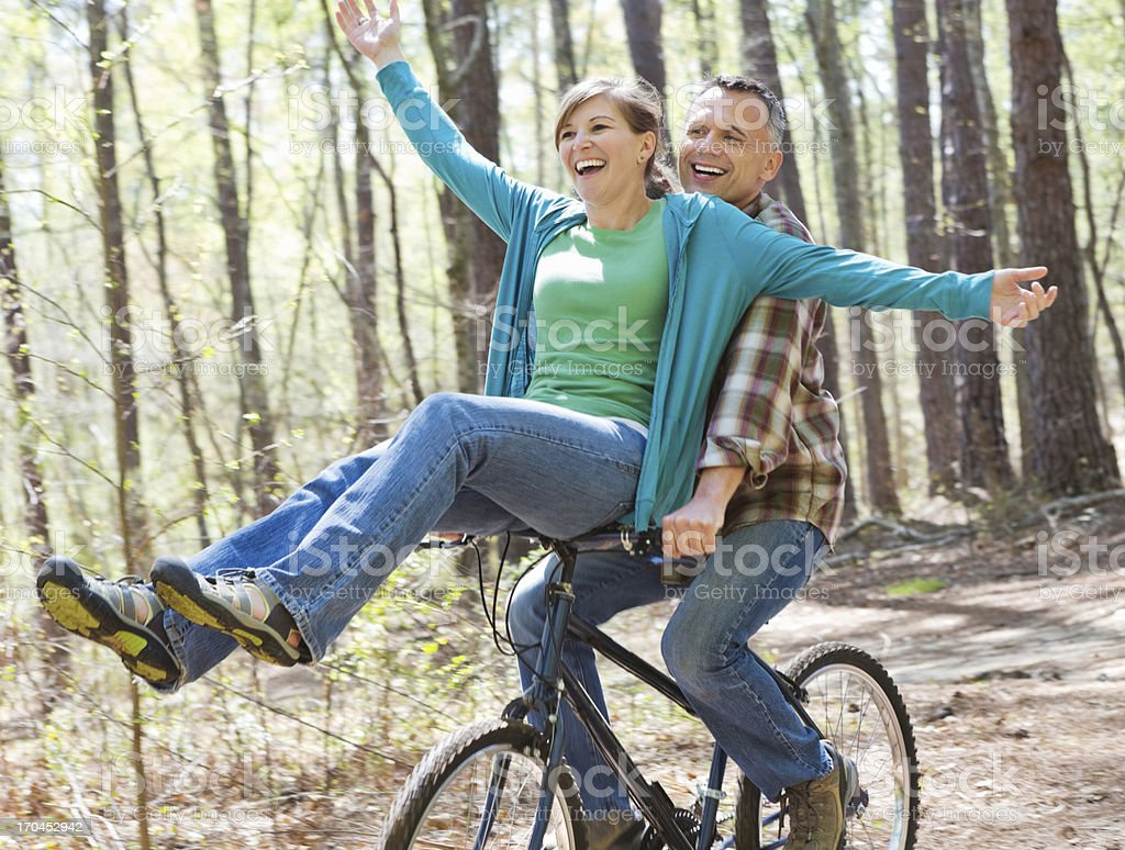 Happy couple riding bicycle together at outdoor park stock photo