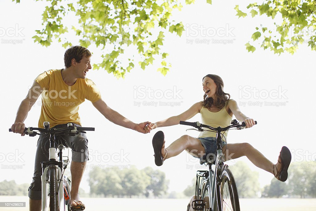 Happy couple riding bicycles and holding hands stock photo
