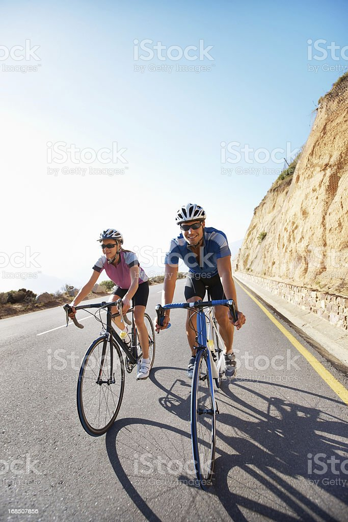 Happy couple riding bicycles on a mountain road royalty-free stock photo