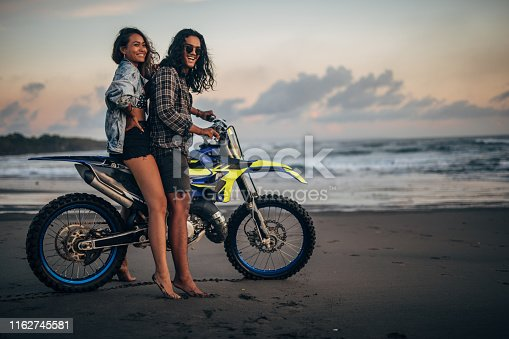 Man and woman, young couple on the beach, riding on a motorcycle together.