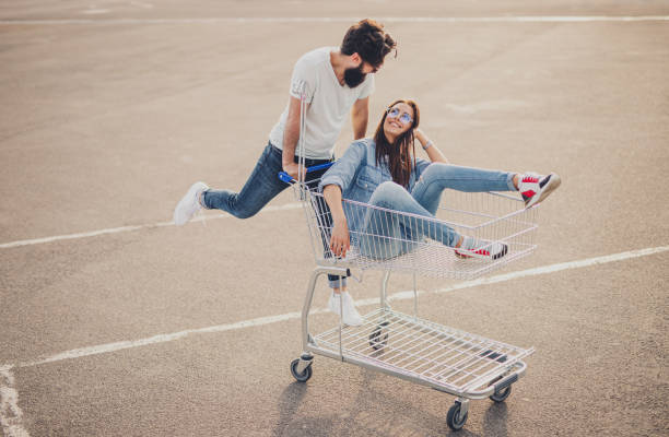 Happy couple riding shopping trolley stock photo