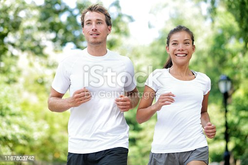 Fitness healthy lifestyle. Happy couple running summer training for marathon in Central Park Manhattan, New York. Asian female model and Caucasian sport fitness male athlete enjoying jogging together.