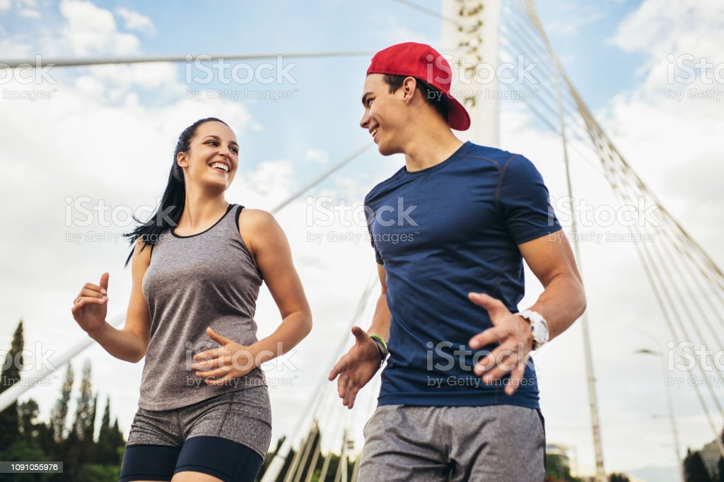 Happy Couple Running Across The Bridge Healthy Lifestyle