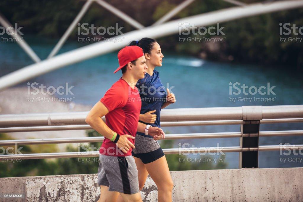 Happy couple running across the bridge. Healthy lifestyle. royalty-free stock photo
