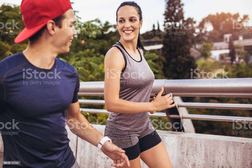 Happy couple running across the bridge. Healthy lifestyle. royalty-free stock photo