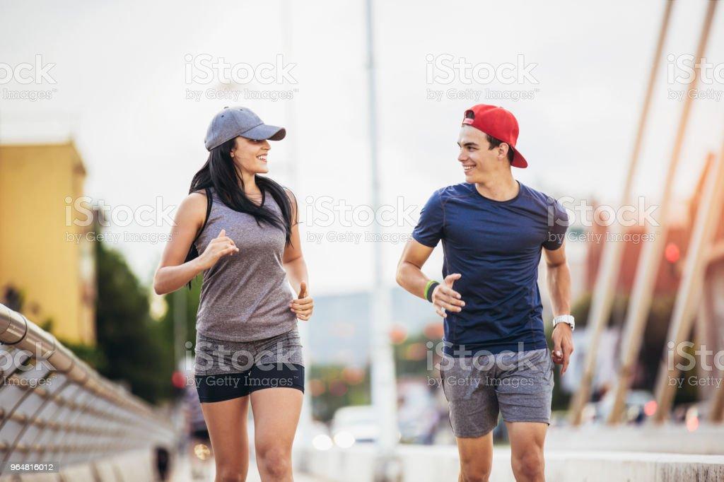 Happy couple running across the bridge. royalty-free stock photo