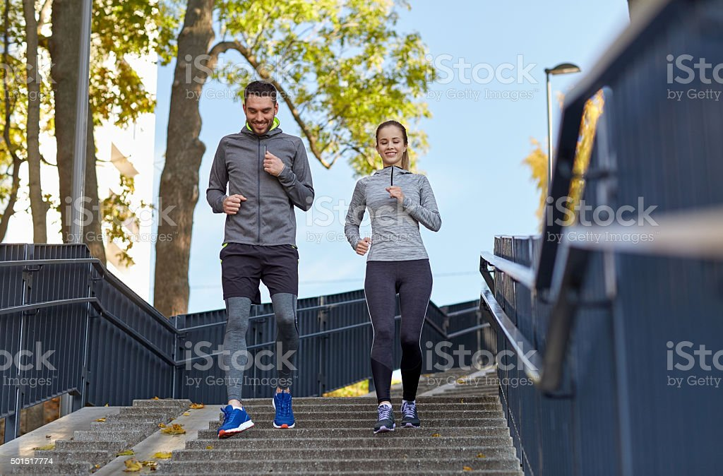happy couple running downstairs in city stock photo