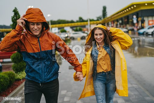 Cheerful young couple in a hurry, running in the city on a rainy day