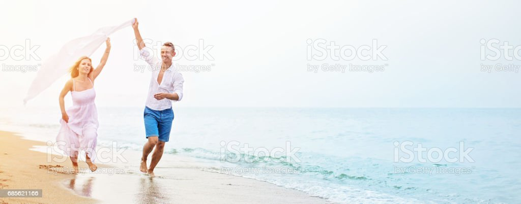 Happy couple running on the beach royalty-free 스톡 사진