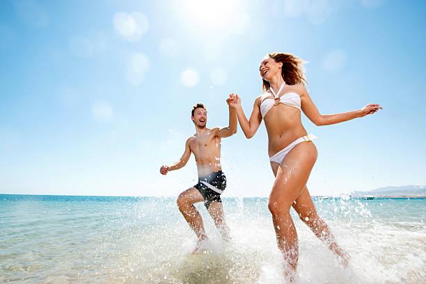 Glückliches Paar Laufen durch das Meer. – Foto