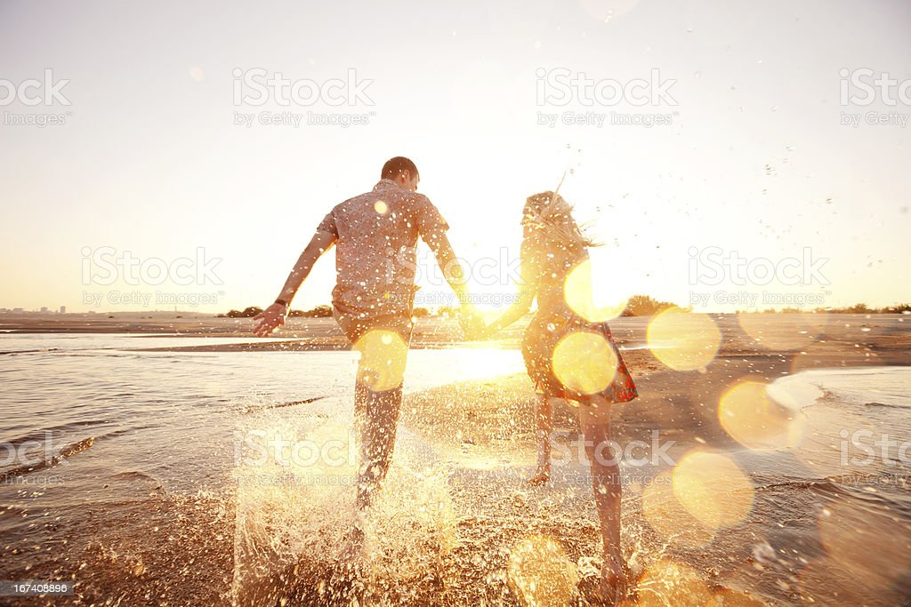 A happy couple runs through waves on sunlit beach stock photo