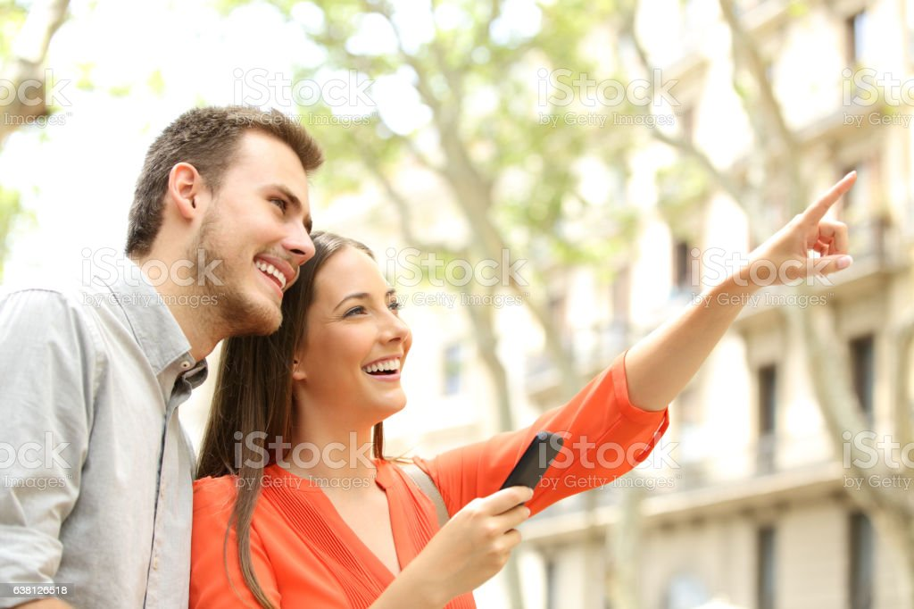 Happy couple searching home in the street stock photo