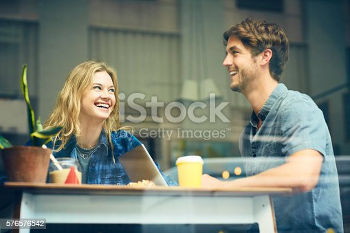 Happy couple sitting at table in cafe. Young man and woman are enjoying hanging out in coffee shop. They are seen through glass window.
