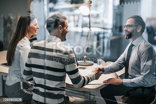 Happy real estate agent shaking hands with young couple after successful meeting in the office. The view is through glass.