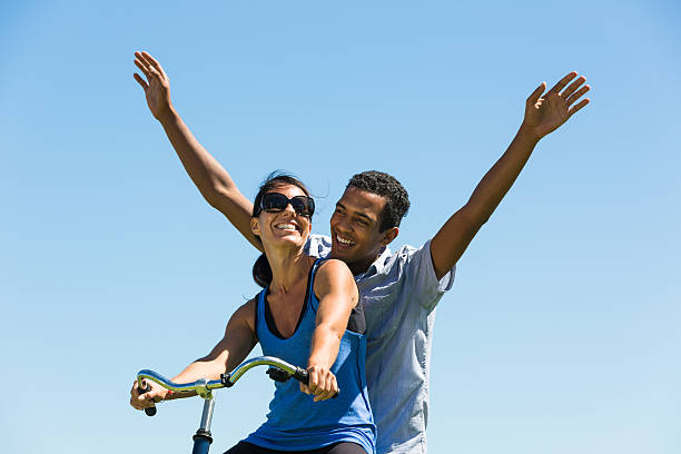 happy couple share a bicycle - carolinemaryan stock pictures, royalty-free photos & images