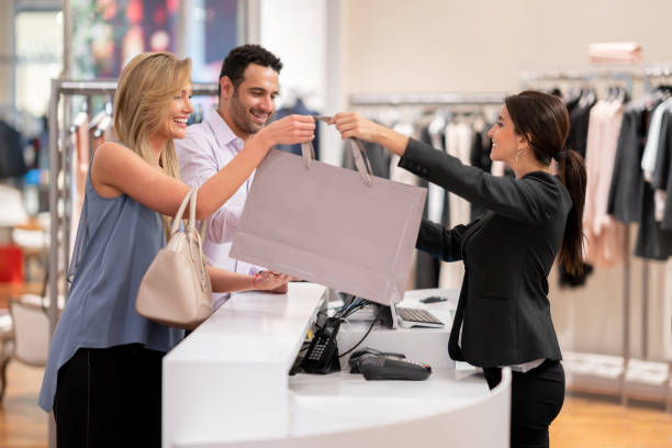 Happy couple shopping at a clothing store Happy couple shopping at a clothing store and paying at the cashier - lifestyle concepts buying stock pictures, royalty-free photos & images