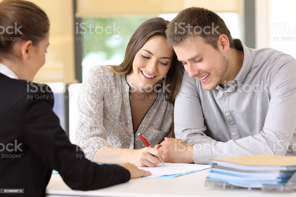 Happy couple signing a contract at office Happy couple signing a contract together at office Adult Stock Photo