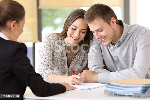 istock Happy couple signing a contract at office 820868610