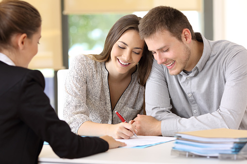 Happy Couple Signing A Contract At Office Stock Photo - Download Image Now
