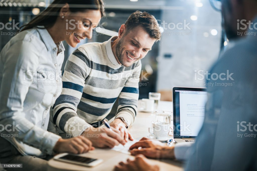 Happy couple signing a contract on a business meeting with their insurance agent. Young happy couple signing a document while being on a meeting with their real estate agent in the office. The view is through glass. Adult Stock Photo