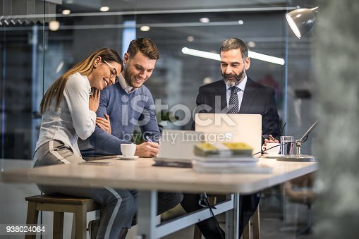 istock Happy couple signing a contract on a business meeting with their insurance agent. 938024064