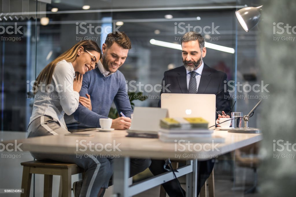 Happy couple signing a contract on a business meeting with their insurance agent. stock photo