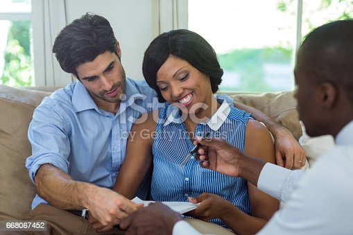istock Happy couple signing contract with real estate agent 668067452