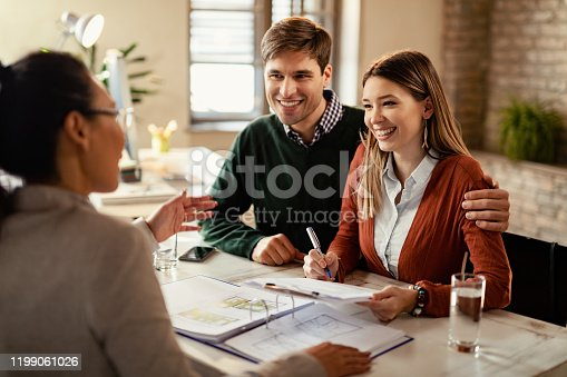istock Happy couple signing mortgage contract while having meeting with real estate agent. 1199061026