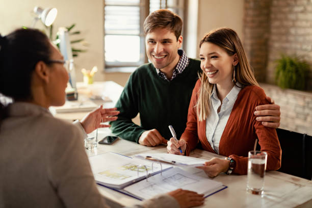 Happy couple signing mortgage contract while having meeting with real estate agent. Young happy couple signing a contract while being on a meeting with insurance agent in the office. mortgages and loans stock pictures, royalty-free photos & images