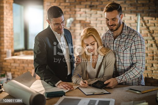istock Happy couple signing the housing contract with the investor. 1039511384