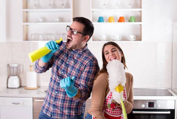 Glückliches Paar singen und tun Hausarbeiten – Foto