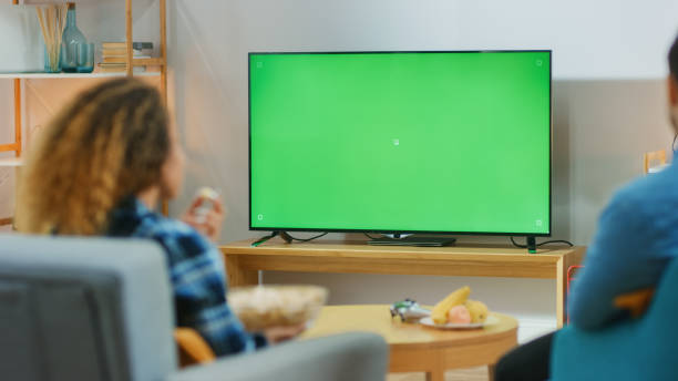 happy couple sitting at home in the living room watching green chroma key screen tv, relaxing on a couch. couple room watching sports match, news, show or a movie. - industria televisiva foto e immagini stock