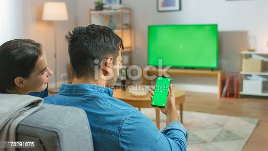 Happy Couple Sitting At Home in the Living Room Watching Green Chroma Key Screen Television, Relaxing on a Couch. Guy also Uses Green Mock-up Screen Smartphone.