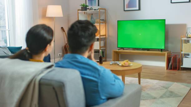 Glückliches Paar sitzen zu Hause beobachten grün Chroma Key Screen Television, Entspannen auf einer Couch. Paar Zimmer beobachten Sport Spiel, Nachrichten, Sitcom TV Show oder ein Film. – Foto