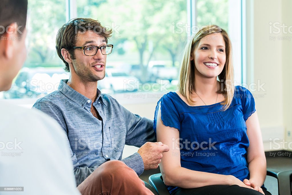Happy couple sitting at meeting together stock photo