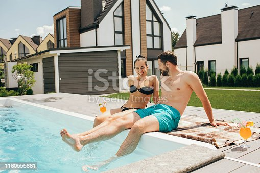Happy couple sitting by the poolside in the backyard of their house. Man and woman sitting near water pool and funny splashing water their legs