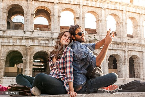 istock Happy couple sitting in front of colosseum in rome taking selfie pictures with smartphone camera. Sunset with lens flare 910932598