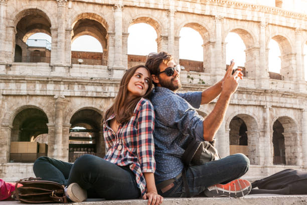 brautpaar sitzt vor dem kolosseum in rom selfie fotografieren mit smartphone-kamera. sonnenuntergang mit blendenfleck - schönen abend bilder stock-fotos und bilder