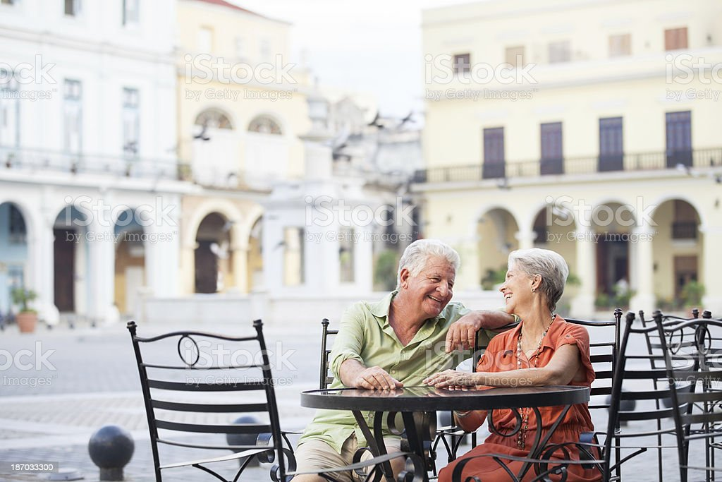 Happy couple sitting in the main square royalty-free stock photo