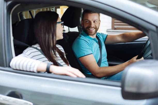 Heureux couple assis dans leur voiture neuve - Photo