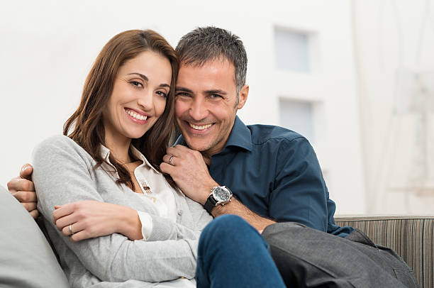 happy couple sitting on couch - mid adult couple stock pictures, royalty-free photos & images