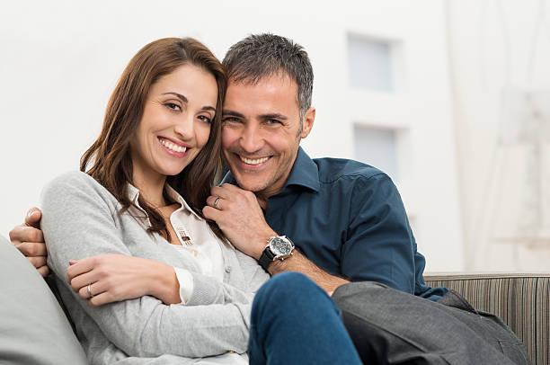 happy couple sitting on couch - mid volwassen koppel stockfoto's en -beelden