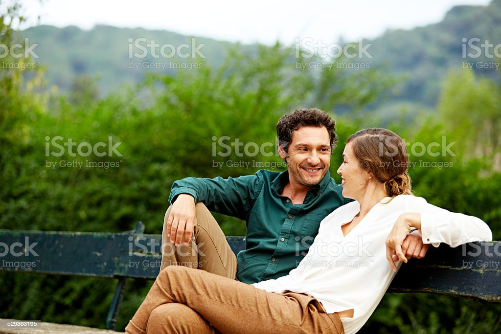 Happy couple sitting on park bench stock photo
