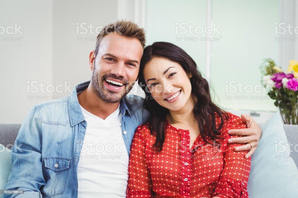 Happy couple sitting on sofa at home – zdjęcie