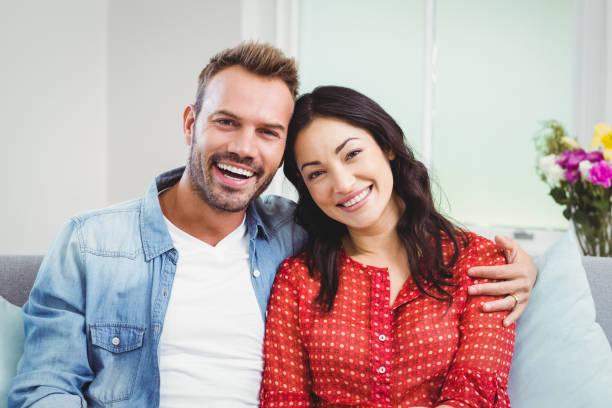 gelukkige paar zittend op de bank thuis - 30 39 jaar stockfoto's en -beelden